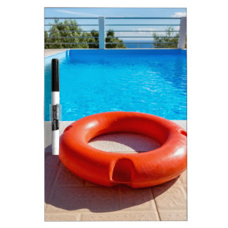 Orange life buoy at blue swimming pool Dry-Erase board