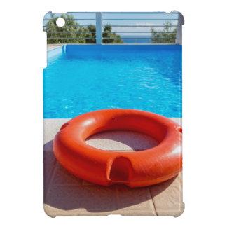 Orange life buoy at blue swimming pool iPad mini covers