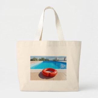 Orange life buoy at blue swimming pool large tote bag