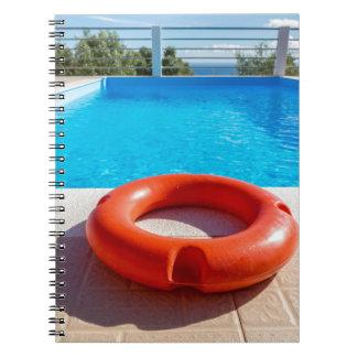 Orange life buoy at blue swimming pool notebooks