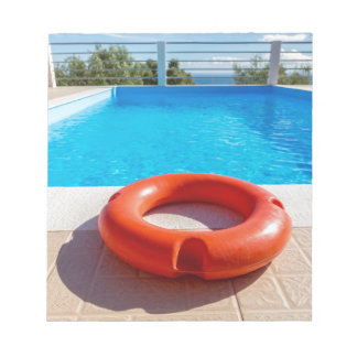 Orange life buoy at blue swimming pool notepad
