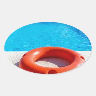 Orange life buoy at blue swimming pool oval sticker