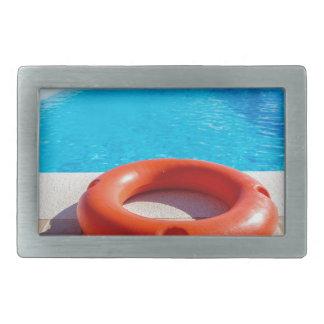 Orange life buoy at blue swimming pool rectangular belt buckles