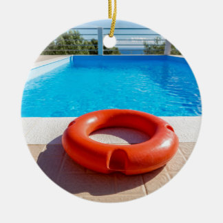 Orange life buoy at blue swimming pool round ceramic ornament