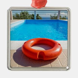 Orange life buoy at blue swimming pool Silver-Colored square ornament