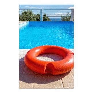 Orange life buoy at blue swimming pool stationery