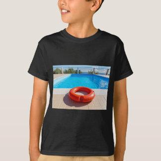 Orange life buoy at blue swimming pool T-Shirt