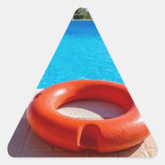 Orange life buoy at blue swimming pool triangle sticker