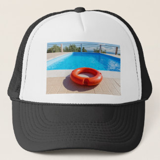 Orange life buoy at blue swimming pool trucker hat