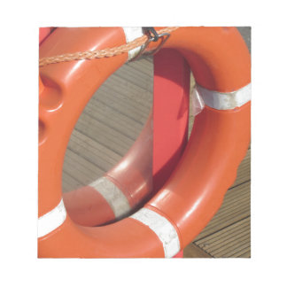 Orange lifebuoy on wooden pier in the harbor notepad