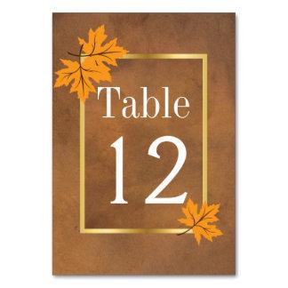 Orange maple leaves on brown wedding table number