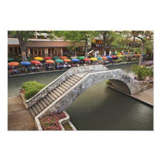 Outdoor cafe along River Walk and bridge over Photograph
