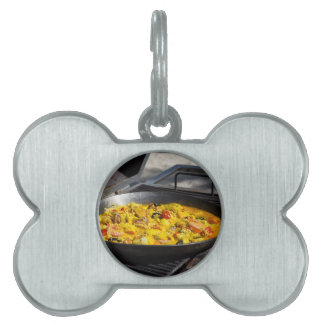 Paella is cooked on a grill pet tag