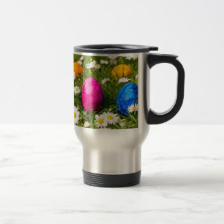 Painted easter eggs in grass with daisies travel mug