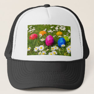 Painted easter eggs in grass with daisies trucker hat
