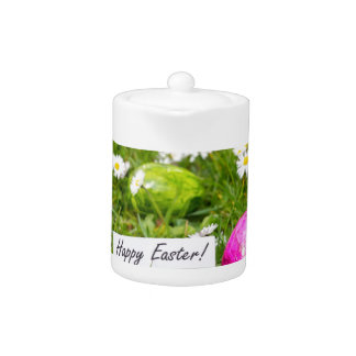 Painted Easter eggs in grass with white daisies