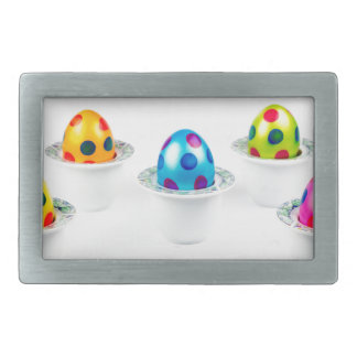 Painted easter eggs standing in porcelain egg cups belt buckles