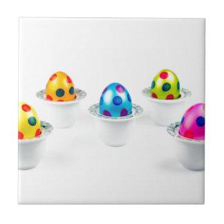 Painted easter eggs standing in porcelain egg cups ceramic tiles