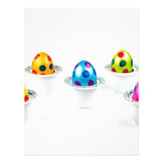 Painted easter eggs standing in porcelain egg cups letterhead