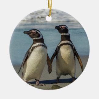 Pair of penguins on the beach round ceramic ornament