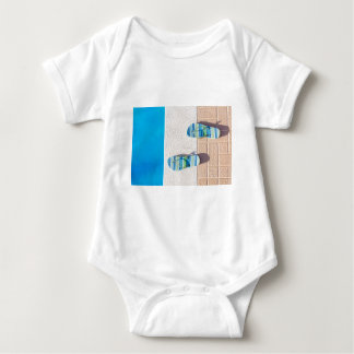 Pair of slippers at edge of swimming pool baby bodysuit