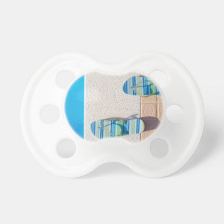 Pair of slippers at edge of swimming pool baby pacifier