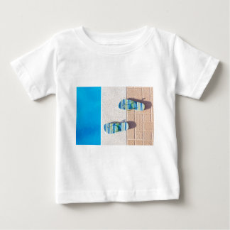 Pair of slippers at edge of swimming pool baby T-Shirt