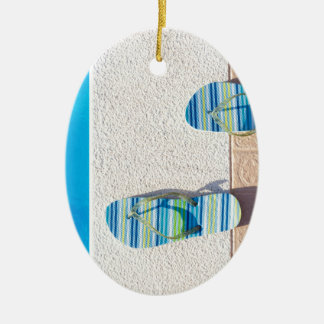 Pair of slippers at edge of swimming pool ceramic oval ornament