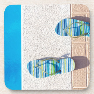 Pair of slippers at edge of swimming pool coaster