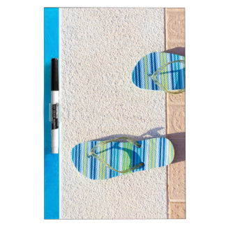 Pair of slippers at edge of swimming pool dry erase white board