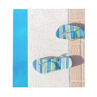 Pair of slippers at edge of swimming pool notepads