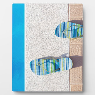 Pair of slippers at edge of swimming pool plaque