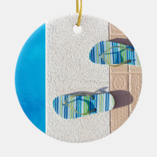 Pair of slippers at edge of swimming pool round ceramic ornament