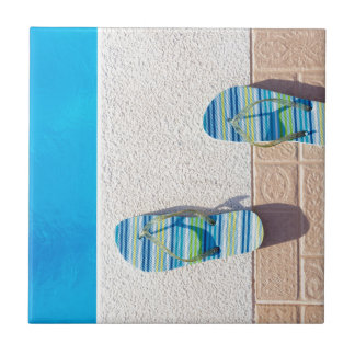 Pair of slippers at edge of swimming pool tile