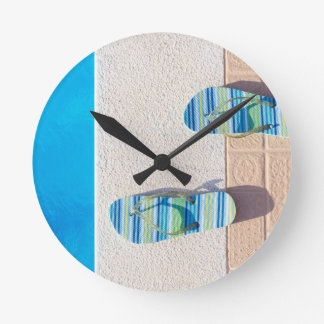 Pair of slippers at edge of swimming pool wall clock