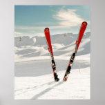 Paires rouges de ski se tenant dans la neige posters