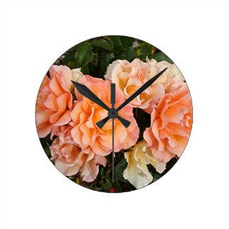 Pale orange roses in bloom in garden wall clock