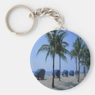 Palm trees, and  cabanas on a beach, on a keychain