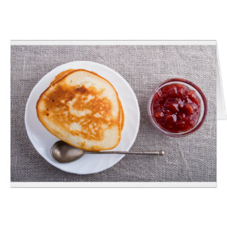 Pancakes and a glass cup with strawberry jam card