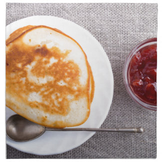 Pancakes and a glass cup with strawberry jam napkin