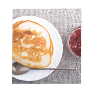 Pancakes and a glass cup with strawberry jam notepad