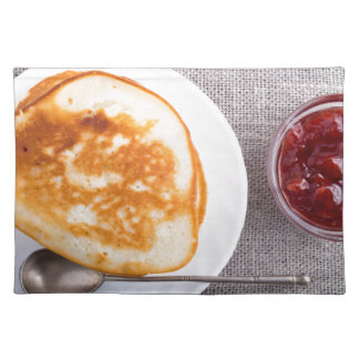 Pancakes and a glass cup with strawberry jam placemat