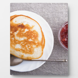 Pancakes and a glass cup with strawberry jam plaque