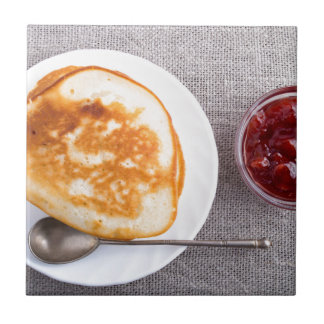 Pancakes and a glass cup with strawberry jam tile