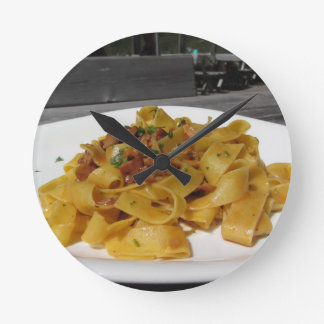 Pappardelle with mushrooms on rustic outdoor table round clock