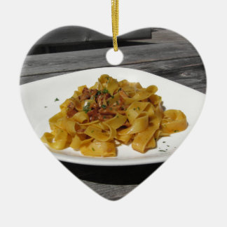 Pappardelle with mushrooms on rustic wooden table ceramic ornament