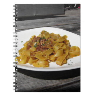 Pappardelle with mushrooms on rustic wooden table notebook