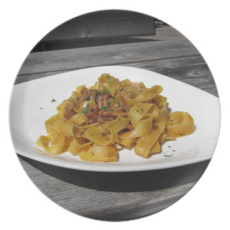 Pappardelle with mushrooms on rustic wooden table plate