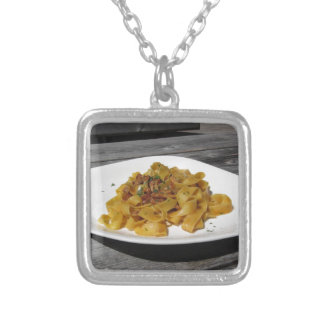 Pappardelle with mushrooms on rustic wooden table silver plated necklace