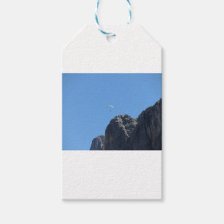 Paraglider with his yellow parachute near mountain gift tags
